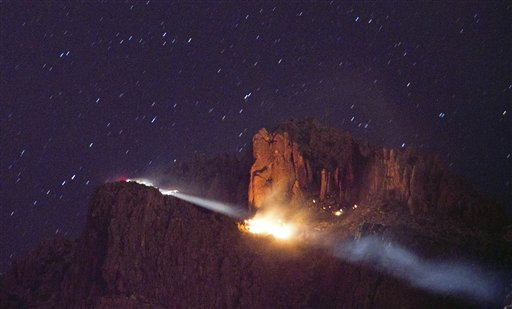 A floodlight illuminates a fire from a small plane crash in the Superstition Mountains in Apache Junction east of Phoenix, Wednesday, Nov. 23, 2011. Authorities said there was no apparent sign of survivors in the small twin-engine plane crash.