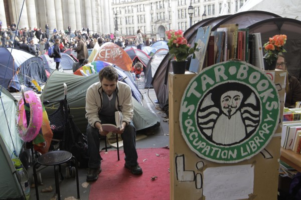 A protester reads a book at the Occupy London camp area outside St Paul's Cathedral in London on Wednesday, Nov. 2, 2011. Anti-capitalist protesters continue to camp on the church's ground after legal actions to evict them were suspended.