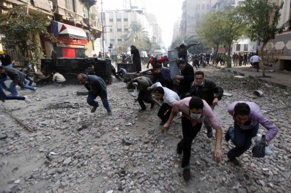 Protesters run for cover during clashes with the Egyptian riot police near Tahrir square in Cairo, Egypt on Tuesday, Nov. 22, 2011. Egypt's civilian cabinet has offered to resign after three days of violent clashes in many cities between demonstrators and security forces, but the action failed to satisfy protesters deeply frustrated with the new military rulers.