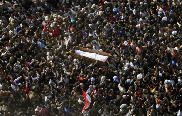Egyptians carry a body of a protester who was killed in clashes with the Egyptian riot police during his funeral at Tahrir square in Cairo, Egypt, Tuesday, Nov. 22, 2011. Egypt's civilian cabinet has offered to resign after three days of violent clashes in many cities between demonstrators and security forces, but the action failed to satisfy protesters deeply frustrated with the new military rulers.