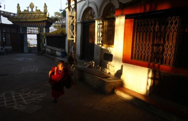A young monk runs inside a Buddhist monastery at Swayambhu, a World Heritage site in Katmandu, Nepal on Tuesday, Nov. 22, 2011.
