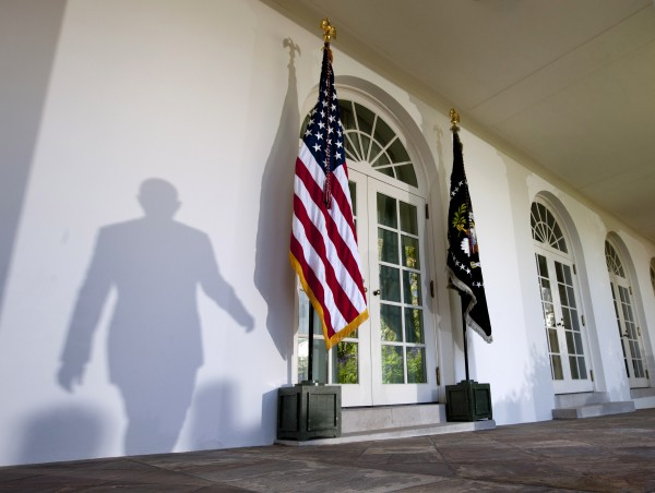 The shadow of President Barack Obama is seen as he arrives to talk about the American Jobs Act, Monday, Nov. 7, 2011, in the Rose Garden of the White House in Washington.