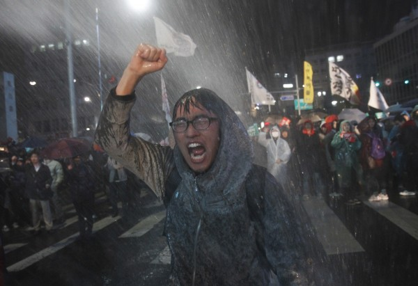 A protester shouts slogans to denounce the passing of a bill on ratification of a South Korea-U.S. free trade agreement as police spray water to disperse the protesters in Seoul, South Korea on Tuesday, Nov. 22, 2011. South Korea's parliament ratified a long-stalled free trade deal with the United States on Tuesday after ruling party lawmakers forced a vote amid shouts and shoves from opposition rivals.