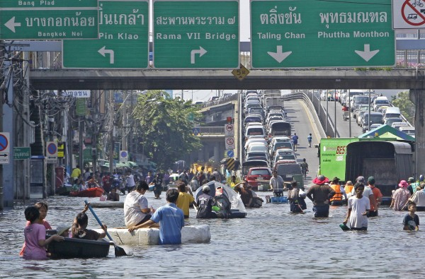 Thai residents wade through floodwaters in the Bang Phlat district of Bangkok, Thailand, Tuesday, Nov. 1, 2011. Higher than normal tides pushing into the Chao Phraya river from the Gulf of Thailand in recent days have complicated efforts to drain floodwaters flowing from the country's central heartland, where vast areas have been submerged for up to two months.