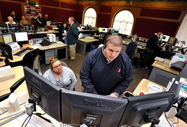 Communications specialist Will Lovejoy (standing) of Dexter and senior supervisor Tracy Hall of Hermon pull up radio logs on the center's computer system as Bangor city councilors take a tour of the Penobscot Regional Communications Center recently.