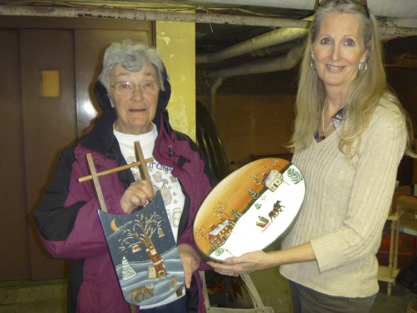 Artist Jean Alderman of Skowhegan shows Kathy Bernier, executive director of the Hammond Street Senior Center, a wooden box and sled she hand painted to donate to the center's upcoming It's a Basket Case silent auction set for Dec. 5-9.