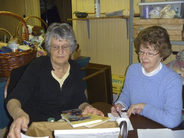Volunteers Gayle Crowley and Sally Polyot, both of Bangor, number and list items in each of the approximately 200 gift baskets that will be up for bid in the Hammond Street Senior Center silent auction Dec. 5-9, at the center.