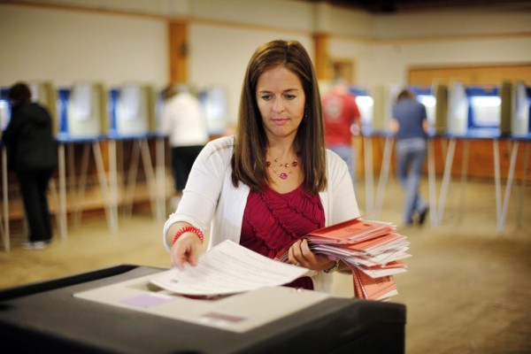 Ward clerk Tina Turgeon feeds absentee ballots into the collection box at a polling place at the Knights of Columbus Hall in Biddeford.