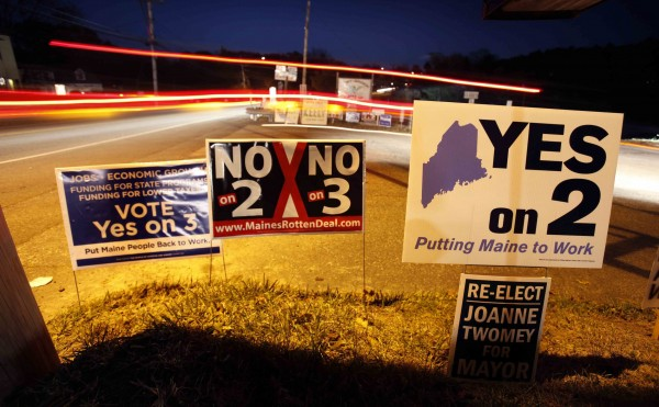 Traffic streams by signs for and against Questions 2 and 3 as voters arrive at a polling place at the Knights of Columbus Hall in Biddeford.