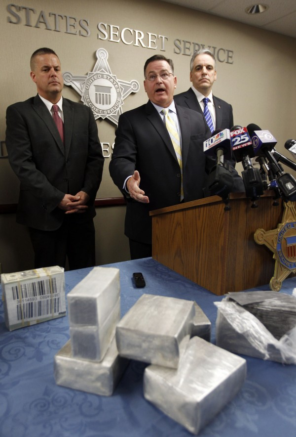 Providence, R.I., Secret Service Resident Agent in Charge Thomas Powers (center) faces reporters as R.I. State Police Captain James Demers (left) and R.I. U.S. Attorney Peter Neronha (right) look on during a news conference at the Secret Service office, in Providence, Thursday, Nov. 3, 2011, as bundles of fake so-called &quotblack money,&quot rest on the table in front.