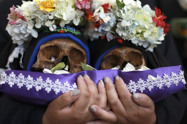 A woman holds a set of decorated human skulls during Dia de los Natitas or Day of the Skulls festivities, before the start of a Mass at the church cemetery in La Paz, Bolivia on Tuesday Nov. 8, 2011. &quotNatitas,&quot are human skulls from unnamed, abandoned graves or departed loved ones, that when cared for and decorated with flowers, cigarettes, coca leaves among other treats, are believed to protect one from evil. The Bolivian ritual marks the end of the All Saints holiday, but is not recognized by the Catholic church.