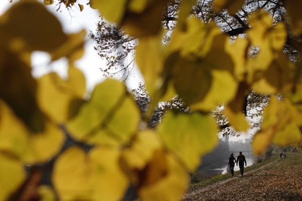 Bosnian people enjoy a sunny Autumn day as they walk on a promenade covered with leaves in Sarajevo, Bosnia on Wednesday, Nov. 2, 2011. Mild weather with average daily temperatures of 18 Celsius will stay until the half of November.