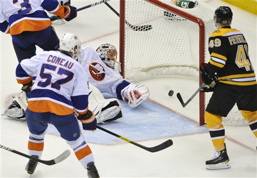 New York Islanders' Blake Comeau (57) and Boston Bruins' Rich Peverley (49) watch the puck shot by Bruins' Chris Kelly get past Islanders goalie Anders Nilsson (45) to score in the third period of an NHL game on Saturday, Nov. 19, 2011, in Uniondale, N.Y.