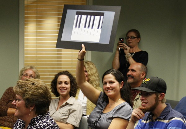 Rachel Rumson holds up a card showing piano keys during an exercise using a live jazz quartet during a business seminar in Portland.