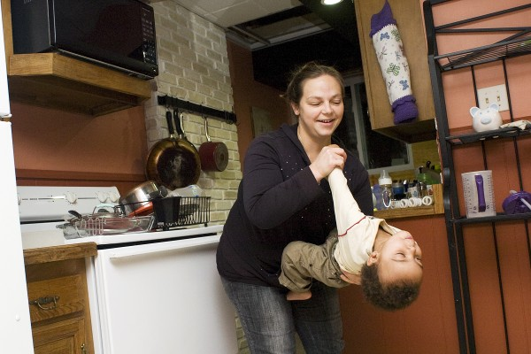 Krystal Johnson plays with her nearly 2-year-old son, Josiah, in the kitchen of their apartment at 279 Pine St. in Lewiston on Wednesday night. Johnson and her three sons returned to their home Wednesday, eight days after an electrical fire forced them to leave. The unit is habitable again, but some work remains to be done, including placing ceiling tiles to cover the hole visible above Johnson's head.