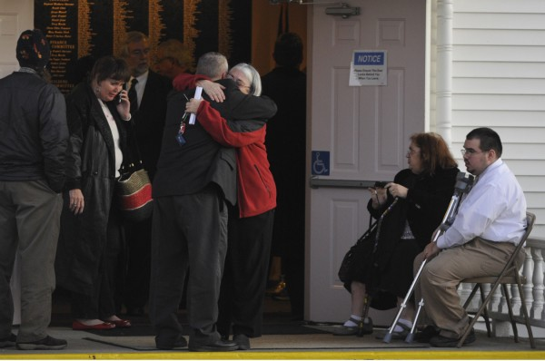 Mourners embrace as they leave East Orrington Congregational Church after the memorial service for Rev. Robert Carlson.
