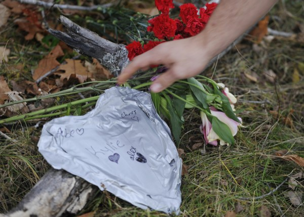 A Hermon High School classmate places a duct tape memorial heart at the crash site on the Irish Road in Carmel where two of his classmates died Monday night. James McPhearson, 16, of Levant and Richard Picken Jr., 14, of Carmel were killed instantly in the crash, according to Maine State Police spokesman Stephen McCausland.