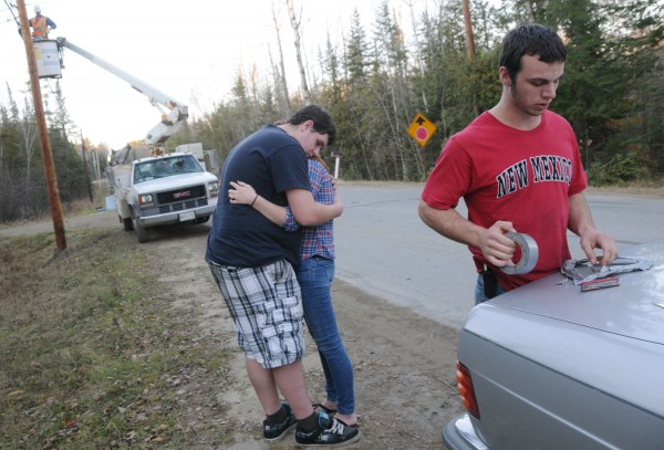 As a friend named Abe (right) works on a makeshift duct tape memorial heart, sophomore Alex Nelson consoles Kylie, a Hermon High School junior classmate, during their Tuesday afternoon visit to the crash site on the Irish Road in Carmel where two of their classmates died Monday night. A utility worker with Fair Point Communications replaces the communications line on the newly replaced utility pole involved in the crash.