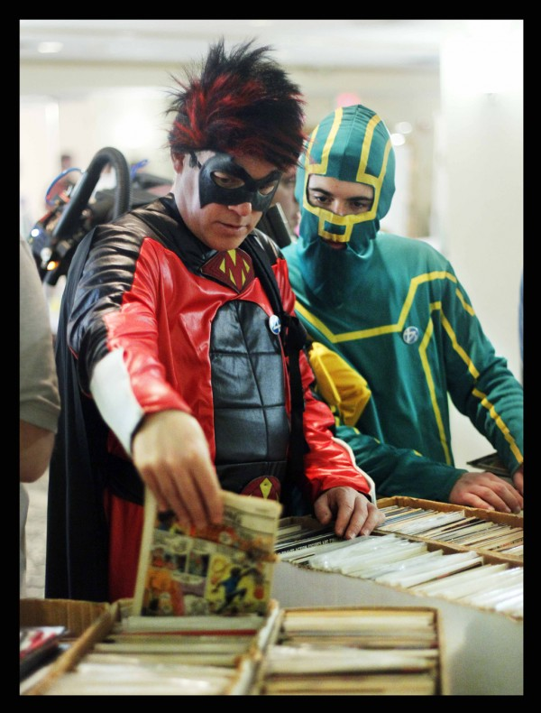 Darren Landry (left), in his Red Mist costume, and his son Cain, dressed as Kick Ass, both of Saco, sort through comics at the Coast City Comicon in Portland on Saturday.