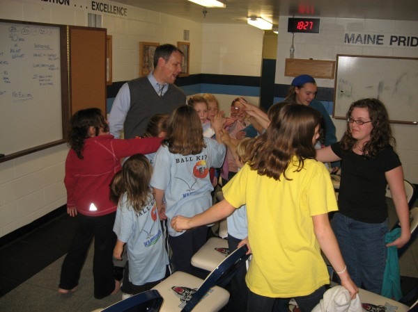 Members of the University of Maine Cub Club Huddle gather for a final cheer to wrap up the session prior to Saturday's Dead River Co. Classic title game against Brown at Alfond Arena in Orono. UMaine women's basketball coach Richard Barron talks with the kids about some key points of  the game.