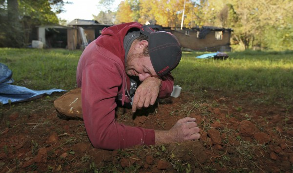 Scott Dunn of Marietta grieves over his dog's freshly dug grave Tuesday, Nov. 1, 2011 in Cobb County, Ga. Dunn's 3½ -year-old boxer Duncan alerted him to a fire Tuesday at Dunn's home but died in the flames. Dunn escaped the fire. Fire officials haven't determined the cause of the blaze.