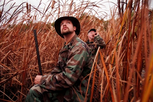 A.J. Guerette (left) watches as high-flying black ducks fail to respond to his father Andy's calls while hunting in the reeds on the shore of the Kennebec River in Bath. A.J. shot his first deer at age 10 while hunting with his dad.. Today, at age 25, he's a registered Maine guide.