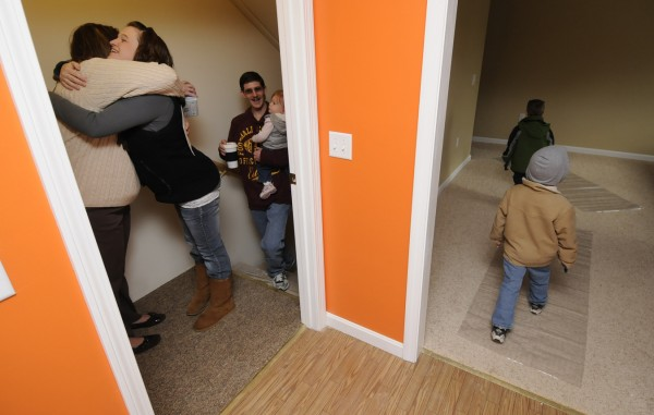 Amanda Charette (left), operations manager for Habitat for Humanity of Greater Bangor, gets a big hug from Lara Hooker as she, her husband David Hooker and their children Naomi,1, James, 5 and Daniel, 4 enter their new Habitat for Humanity-built home on Milford Street in Bangor. A dedication ceremony and celebration for the family took place at the home Saturday afternoon, Nov. 19, 2011.
