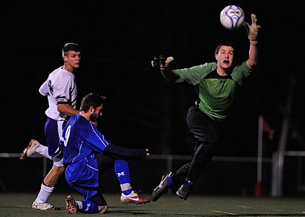 Hampden Academy goal keeper Logan Poirier deflects a score attempt by Messalonskee's Chris Hall (#9) during the second half of their Class A Boys Eastern Maine Soccer Championship in Hampden on Wednesday night, Nov. 2, 2011. On the left is Hampden teammate Kent Reichel.