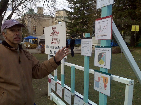 Dennis Chinoy, a Power in Community Alliance member, stands before a wooden structure erected in front of the Occupy Bangor encampment Saturday that depicts the changes in real wages for United States citizens since 1980.