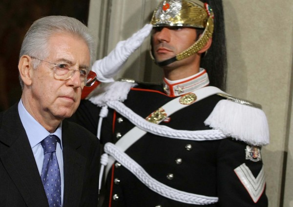 Mario Monti walks past a Cuirassier presidential guard at the Quirinale Presidential Palace in Rome after talks with Italian President Giorgio Napolitano, Sunday, Nov. 13, 2011.