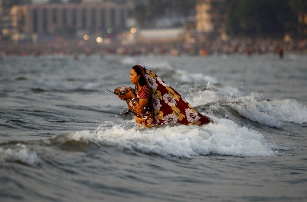 An Indian Hindu women offers prayers to the setting sun during the festival of Chhath at the Arabian Sea, in Mumbai, India, on Tuesday, Nov. 1, 2011.  During this ancient Hindu festival, rituals are performed to thank the Sun god for sustaining life on earth.