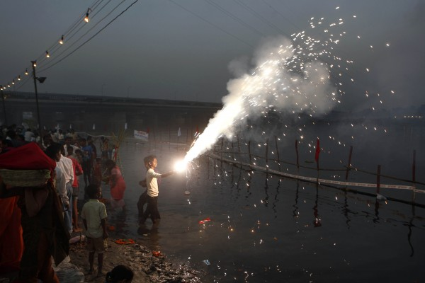 A boy lights fire crackers as Hindu devotees perform rituals in River Yamuna at sunset during Chhath Puja festival in New Delhi, India on Tuesday, Nov. 1, 2011. During Chhath, an ancient Hindu festival, rituals are performed to thank the Sun god for sustaining life on earth.