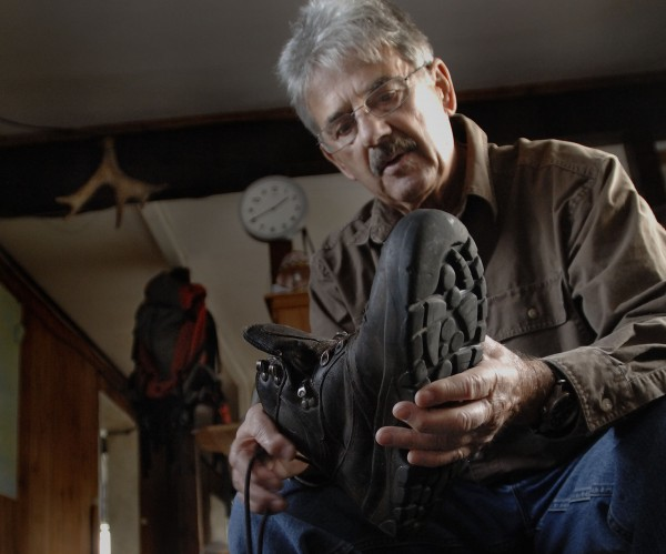 Nelson Daigle talks about the boots he has worn out over the years at his Millinocket home on Nov. 18, 2011. Daigle has hiked Maine's tallest mountain more than 400 times and has done it over the past 17 years.