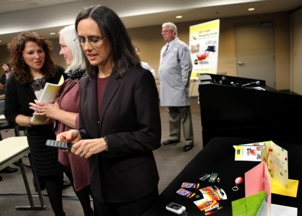 Illinois Attorney General Lisa Madigan holds a press conference in Chicago, Illinois, November 21, 2011, about the dangers of button batteries, which are used in everything from singing greeting cards to t-shirts to remote control devices that Madigan is inspecting here.