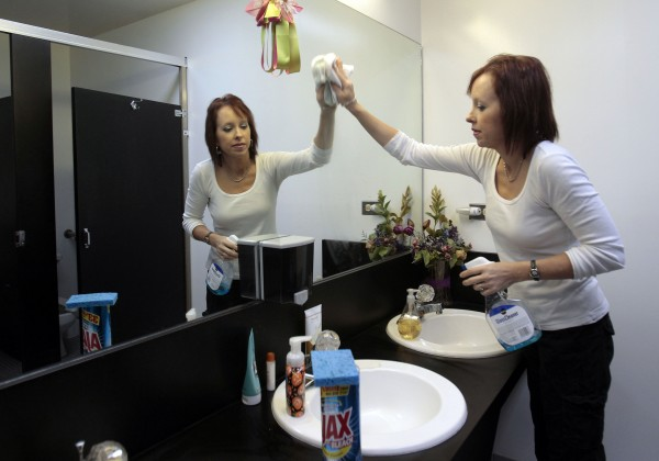 Michelle Hartman, an elementary school  language arts and science teacher, cleans a mirror at an accounting firm in Oakland Park, Fla., last month The single mother has a master's degree in educational leadership and has been a teacher 15 years. But she says she cannot afford to leave any of her additional jobs.
