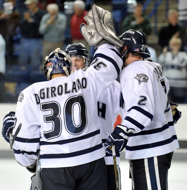 New Hampshire goal tender Matt DiGirolamo is congratulated by teammates, including Connor Hardowa (2), following their 3-2 victory over Maine in an NCAA college hockey game at the Whittemore Center Arena in Durham, N.H., Saturday, Nov. 5, 2011.