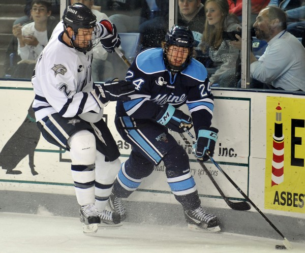 Maine forward Mark Anthoine (24) looks to pass as New Hampshire defenseman Connor Hardowa (2) closes in during the first period of a NCAA college hockey game at the Whittemore Center Arena in Durham, N.H., Saturday, Nov. 5, 2011.