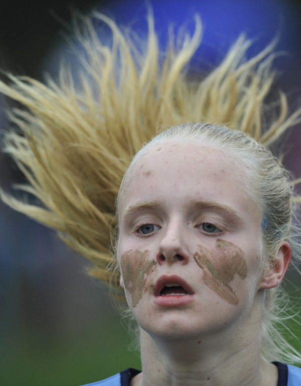 Whimsically sporting her mud &quotwar paint,&quot Riley Simmons of Oceanside High School (Rockland) kicks to the finish of the Maine Festival of Champions 5000 meter cross country race in Belfast Saturday, Oct. 1, 2011.