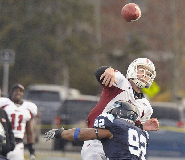 Massachusetts' quarterback Raymond Pendagast (14) gets a pass off in the grasp of Maine's Raibonne Charles (92) during the second half of an NCAA football game in Orono, Maine, Saturday Nov. 12, 2011.