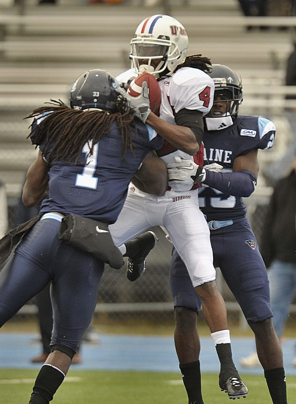 Massachusetts' Jesse Julmiste (4) hauls in a touchdown reception between Maine defenders Vinson Givens (1) and Darlos James (29)  in the first half of an NCAA college football game in Orono, Maine, Saturday, Nov.12, 2011.