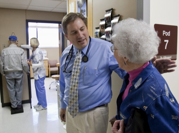 Primary care physician Dr. Don Klitgaard greets Muriel Bacon as her husband weighs in with a nurse at the Myrtue Medical Center in Harlan, Iowa, in this Oct. 26, 2009, file photo. Unless Congress acts before Jan. 1, doctors will again face steep Medicare cuts that threaten to undermine health care for millions of seniors and disabled people.