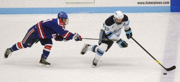 The University of Maine's Spencer Abbott (right) and UMass Lowell's Stephen Buco battle for the puck during the second period at Alfond Arena in Orono Saturday night.