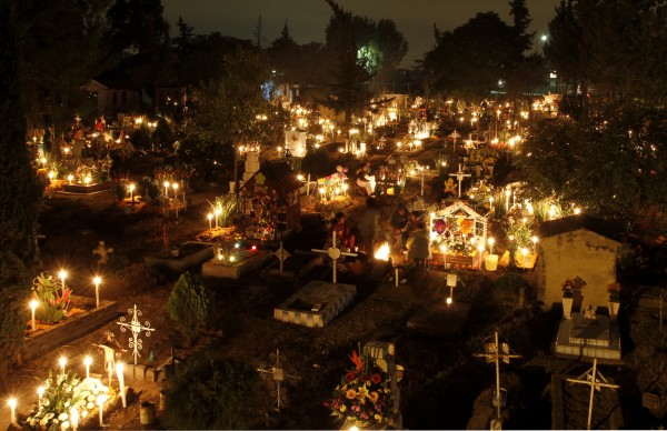 Candles illuminate grave sites at the San Gregorio cemetery during the Dia de los Muertos or Day of the Dead holiday on the outskirts of Mexico City on Tuesday Nov. 1, 2011. A tradition that coincides with All Saints Day and All Souls Day on Nov. 1 and 2., families take picnics to the cemeteries and decorate the graves of departed relatives with marigolds, candles and sugar skulls.