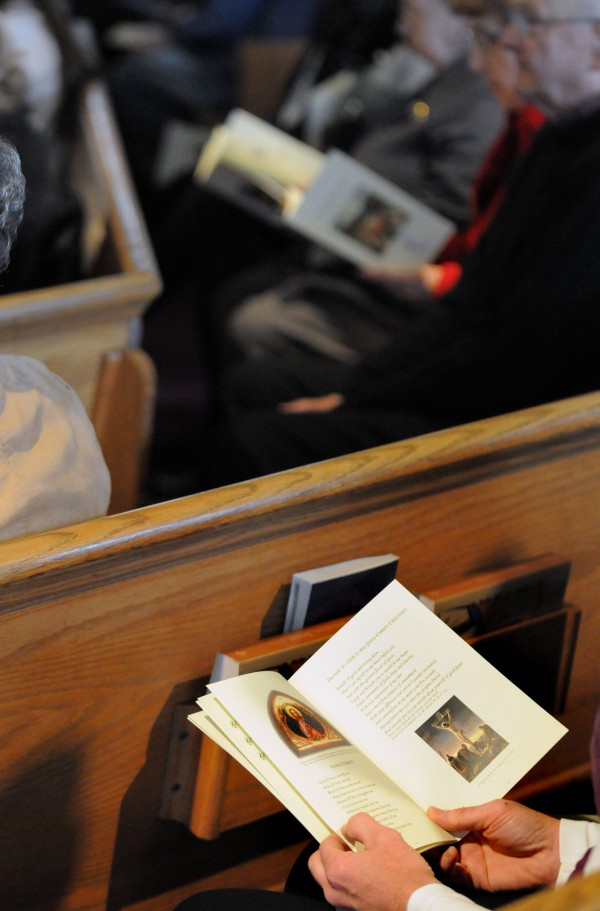 Parishioners at St. Matthew Catholic Church in Hampden look at the new Order of Mass booklets during Sunday service.