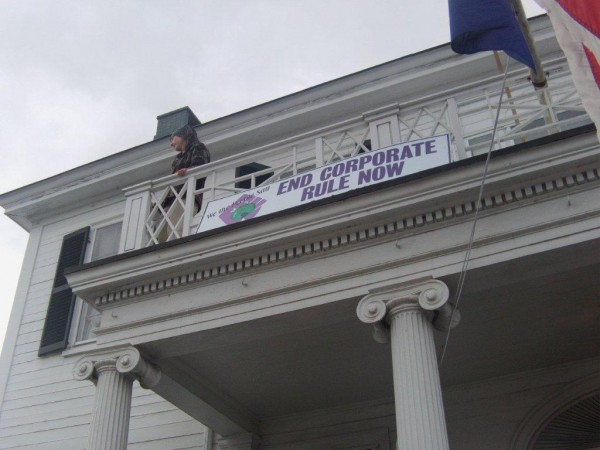 Protesters unfurled a banner on the Governor's mansion that read &quotEnd corporate rule now.&quot