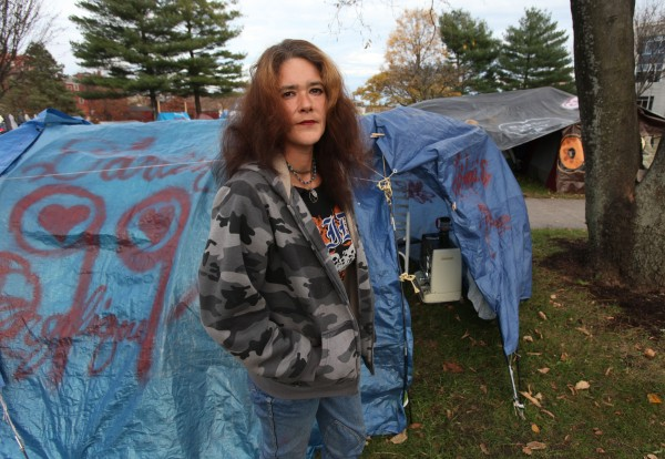 OccupyMaine protester Angelique Banks poses Tuesday, Nov. 15, 2011 in Lincoln Park in Portland, Maine outside of her tent that is insulated and has a portable kerosene heater.