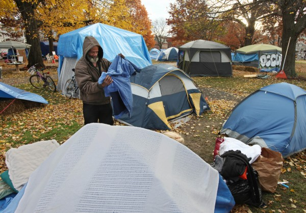OccupyMaine protester Paco Ricks, folds a jacket after leaving it out to dry Tuesday, Nov. 15, 2011 in Lincoln Park in Portland, Maine.