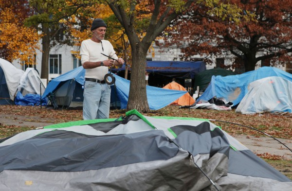 Mike Jacob repairs a tent pole for a fellow OccupyMaine protester Tuesday, Nov. 15, 2011, in Lincoln Park in Portland, Maine.