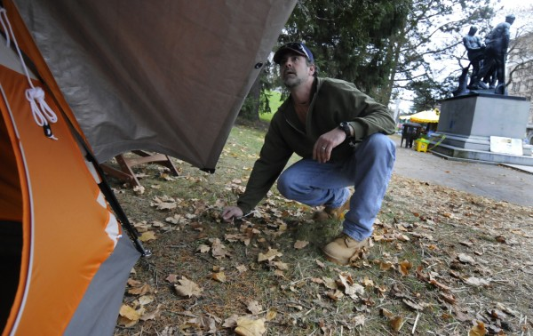 An Occupy Bangor participant, who witheld his name, lines up the rain fly on his tent Wednesday afternoon, Nov. 16, 2011, to weatherize it for the colder weather.