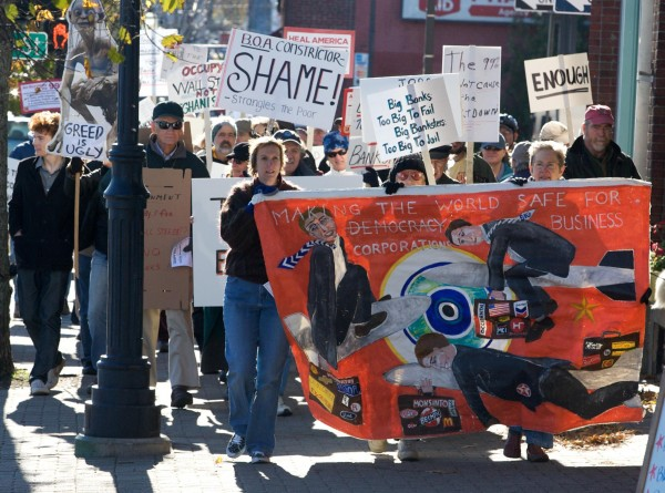 Occupy Brunswick marchers make their way down the sidewalk on Maine Street in Brunswick on Saturday, headed for the Bank of America branch.